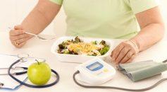 Elderly woman eating healthy diet, salad and apple.